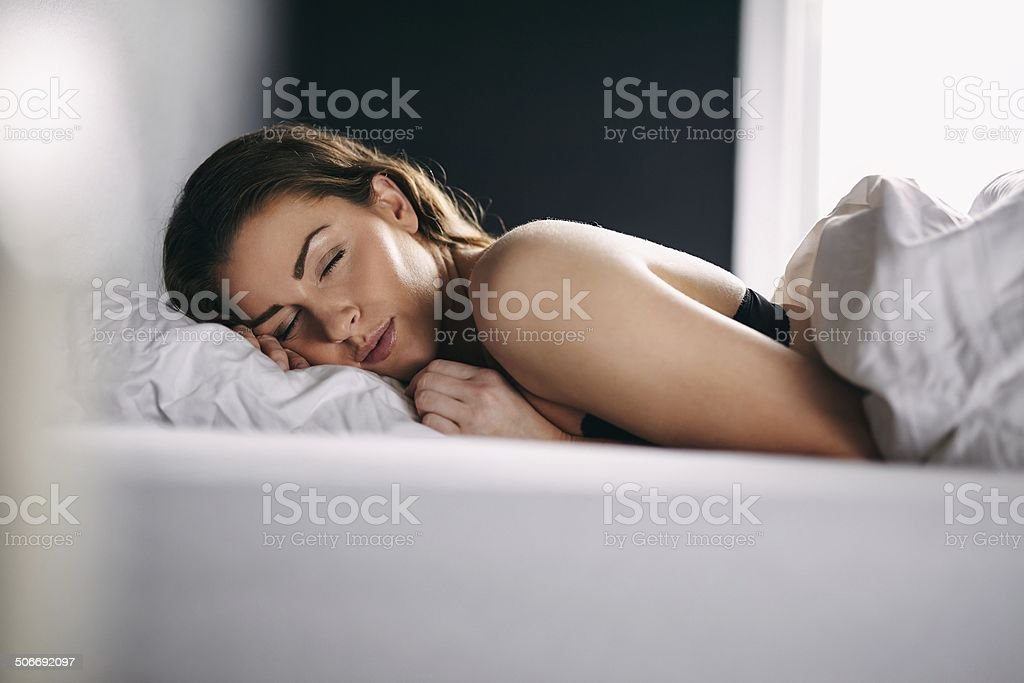 Young woman sleeping peacefully in her bed stock photo