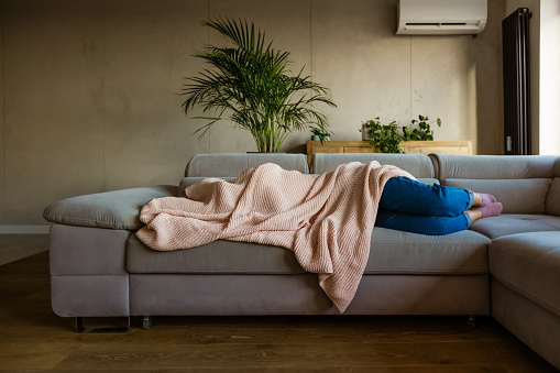 Young woman lying down on sofa in living room covered by blanket. Unrecognizable person.