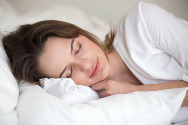 Young woman sleeping well lying asleep in comfortable cozy bed Young woman with beautiful face sleeping well on white cotton sheets and soft pillow lying asleep in comfortable cozy bed at home or hotel enjoying healthy nap resting enough for good relaxation deep stock pictures, royalty-free photos & images