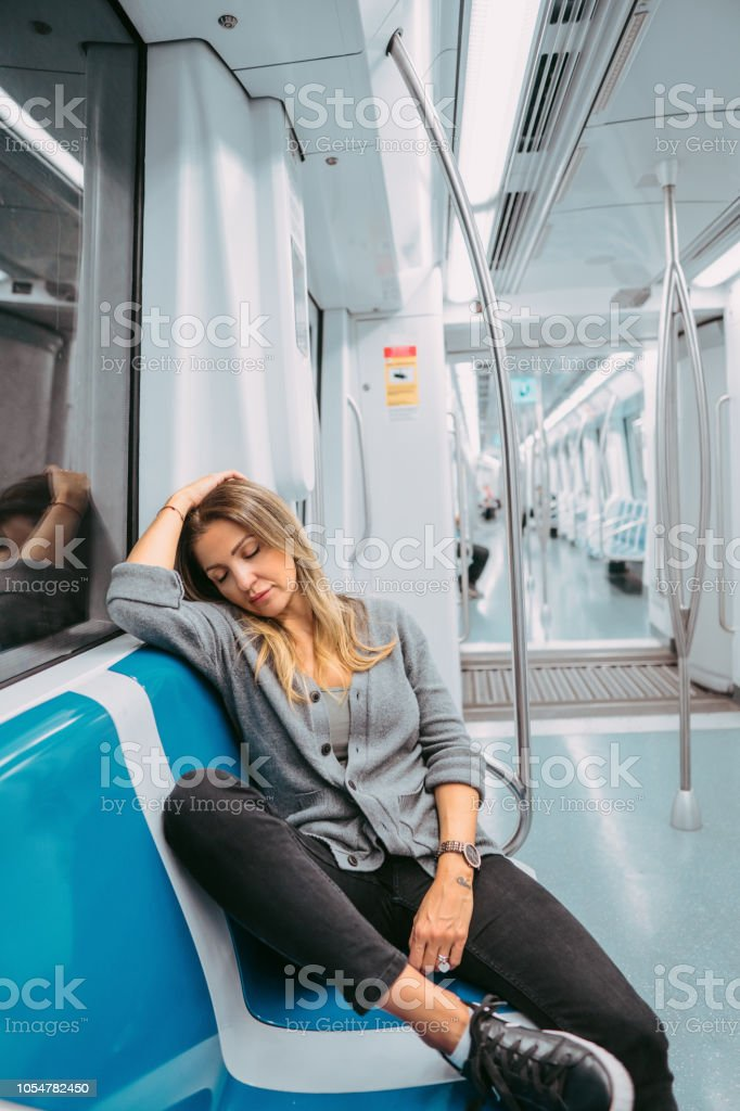 Young woman sleeping while commuting stock photo