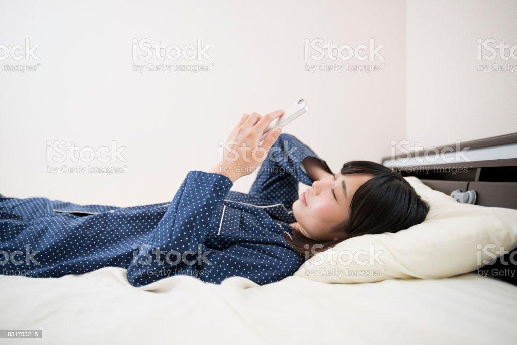 携帯電話で寝ている若い女性 ストックフォト