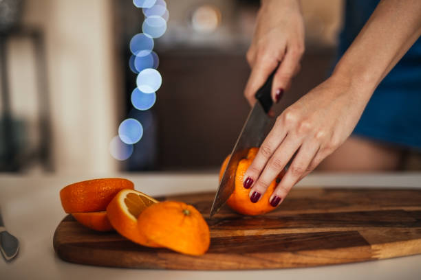 young woman slicing orange in her kitchen - milan2099 stock photos and pictures
