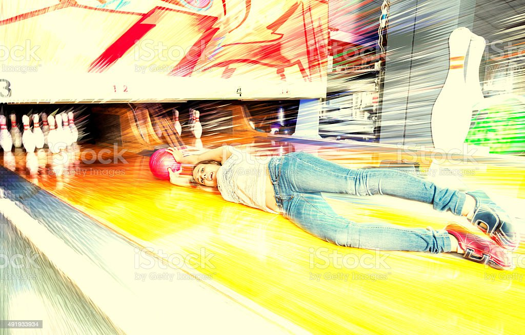 young woman sliding down a bowling alley stock photo