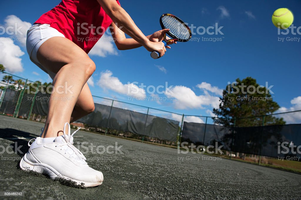 Young woman sliding into a backhand volley stock photo