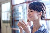 若い女性はコーヒーの香りを嗅ぐ