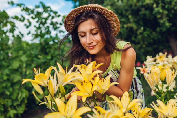 Young woman smelling flowers in garden. Gardener taking care of lilies. Gardening concept