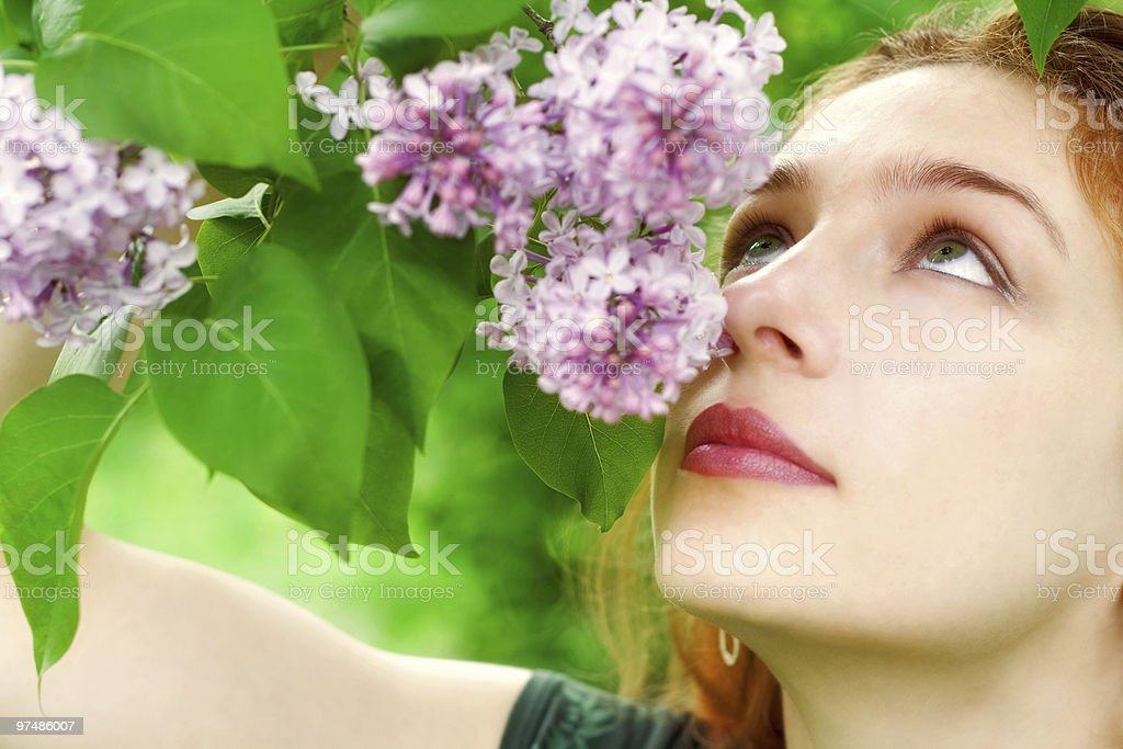 Young woman smelling lilac blossoms royalty-free stock photo