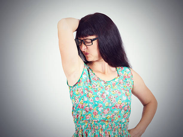 young woman, smelling, sniffing her wet armpit, something stink - ugly girl stock photos and pictures