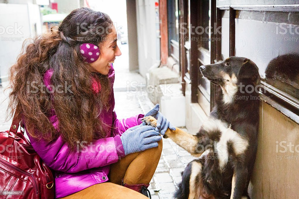 Young woman smiles and holds stray dog paw stock photo