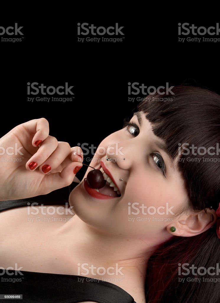 Young woman smiles as she bites a cherry. royalty-free stock photo