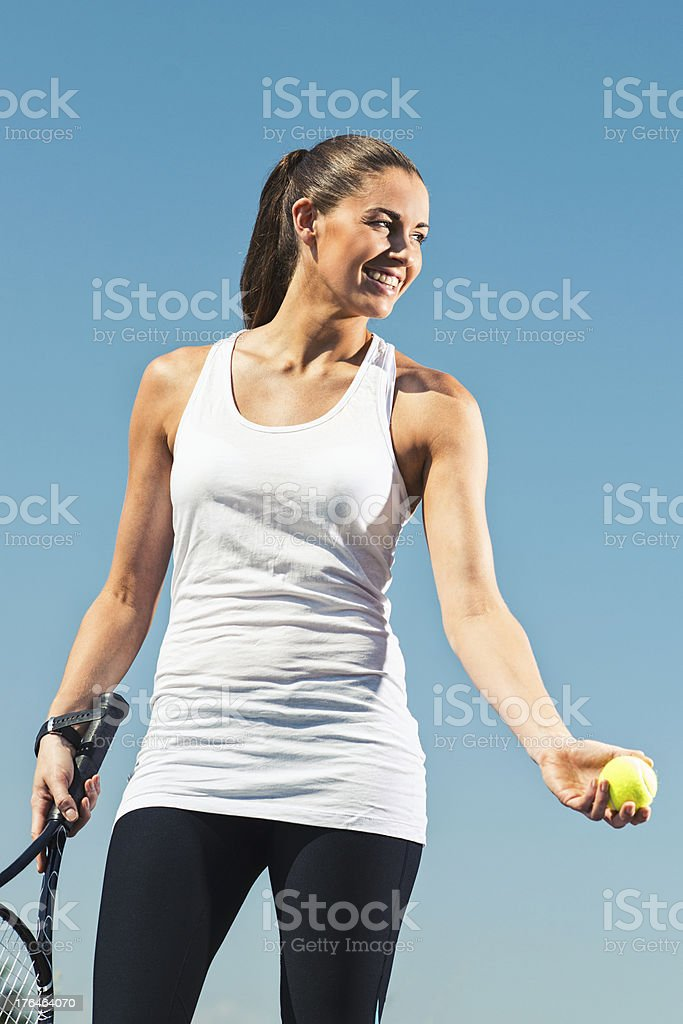 Young woman smiles while playing tennis royalty-free stock photo