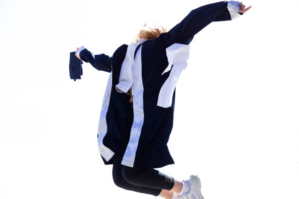 Young woman smiley graduate student in gown jumping stock photo