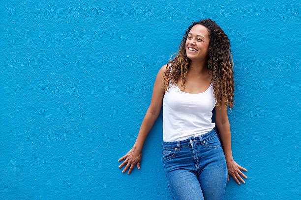 Young woman smiling against blue background stock photo