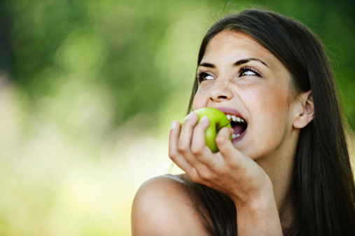 Young woman smiling and biting an apple