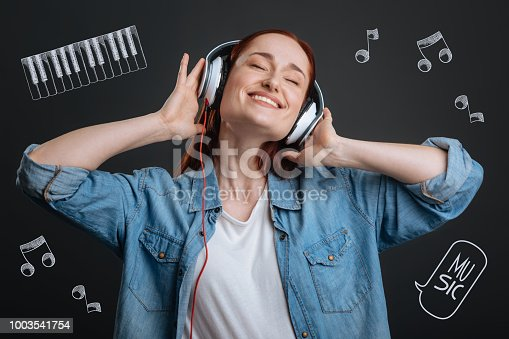 1003539592istockphoto Young woman smiling and closing her eyes while listening to music 1003541754