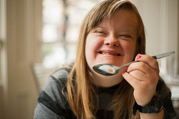 Young woman smiling and holding up spoon stock photo