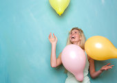 istock Young woman smiling and playing with balloons 491873847