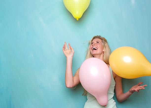 mulher jovem sorridente, brincando com balões - mulher balões imagens e fotografias de stock