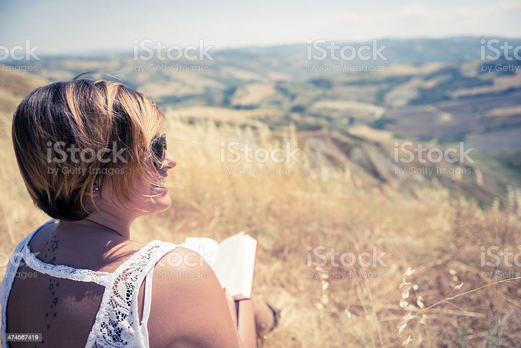 Young woman smiling and reading a book royalty-free stock photo