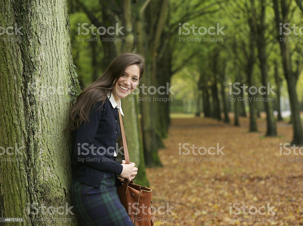 Young woman smiling and relaxing outdoors on an autumn day royalty-free stock photo
