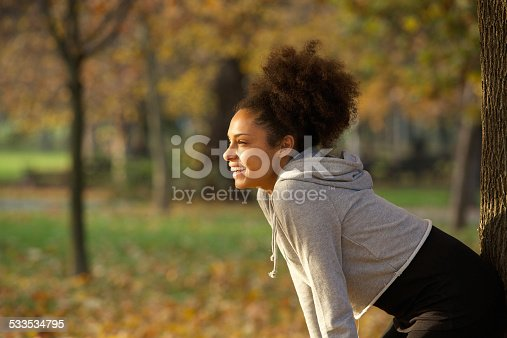 istock Young woman smiling and resting after workout in the park 533534795