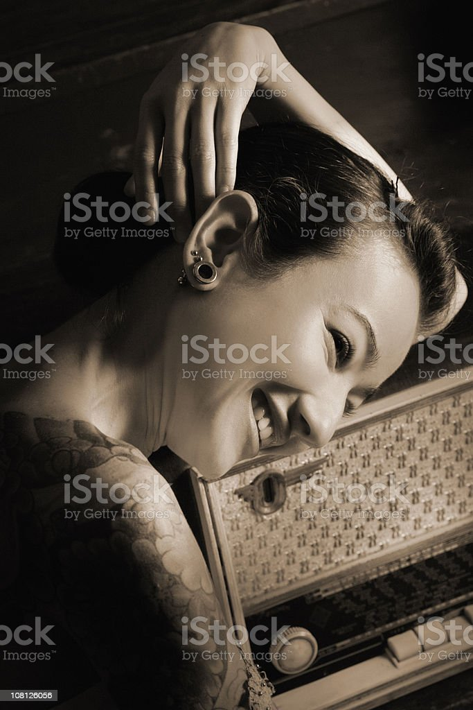 Young Woman Smiling and Resting Head on Antique Radio stock photo