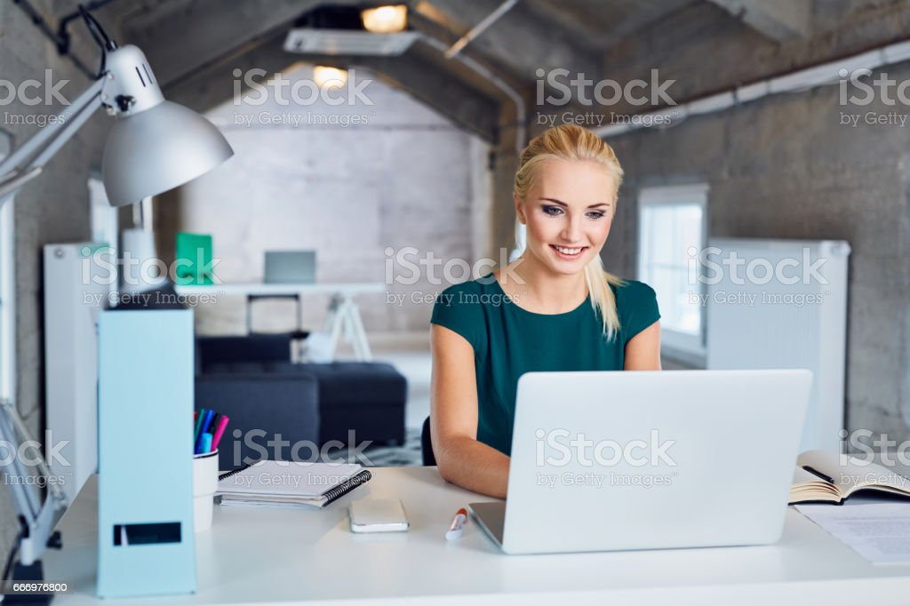 young woman smiling and typing on laptop in modern office stock photo