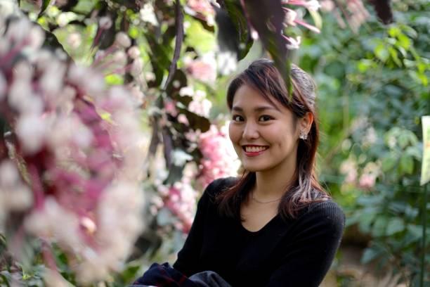在公園微笑的年輕婦女圖像檔