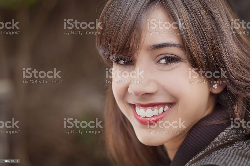 Young woman smiling brown background stock photo