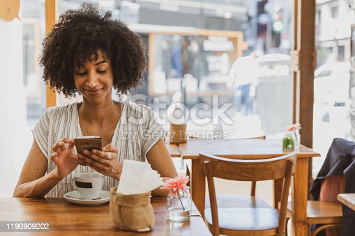 946192604 istock photo Young woman smiling during coffee break chatting on mobile 1190909202