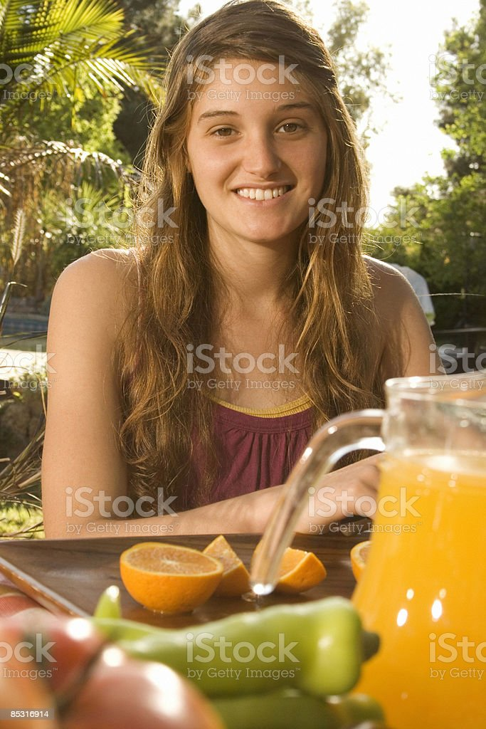 Young woman smiling in front of her fresh oranges royalty-free stock photo
