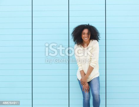istock Young woman smiling on blue background 488264911