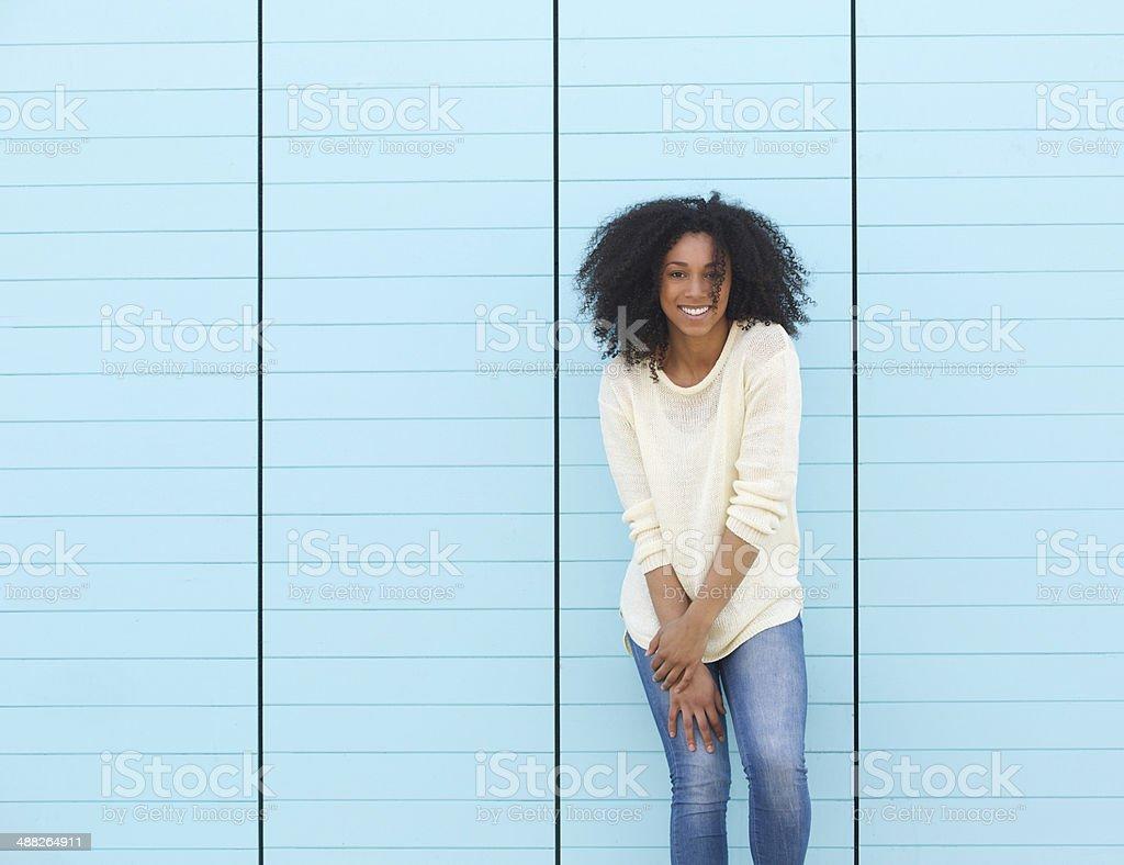Молодая женщина, улыбающаяся на синем фоне стоковое фото