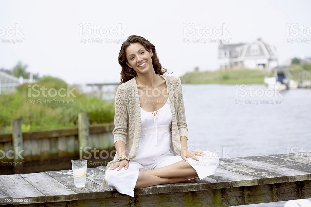 Young woman smiling on dock with beverage, portrait stock photo