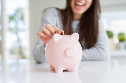 istock Young woman smiling putting a coin inside piggy bank as savings for investment 1143703662