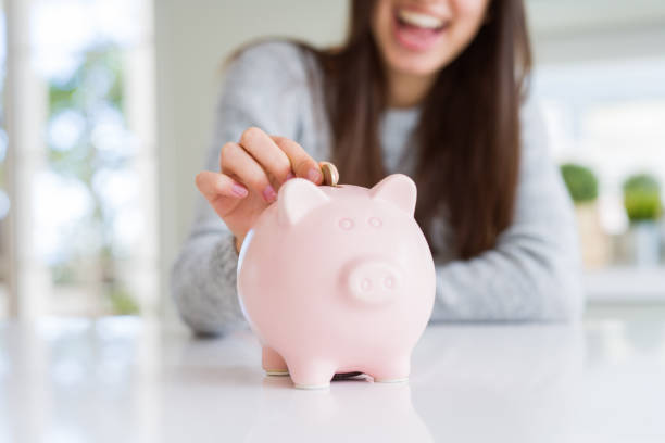 young woman smiling putting a coin inside piggy bank as savings for investment - white background стоковые фото и изображения