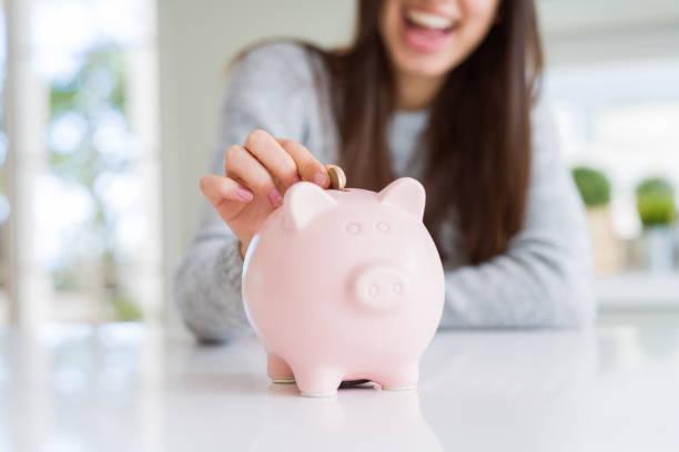 jonge vrouw glimlachen zetten een munt binnen spaarpot als spaargeld voor investeringen - investering stockfoto's en -beelden