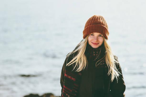 Junge Frau lächelt, Wandern im Winter-Meer-Reisen Mode Lifestyle-Konzept im Freien. Mädchen tragen orange Mütze und Schal Kälte – Foto
