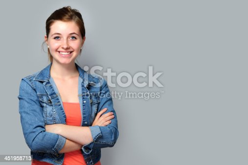istock Young woman smiling wearing denim jacket with arms folded 451958713