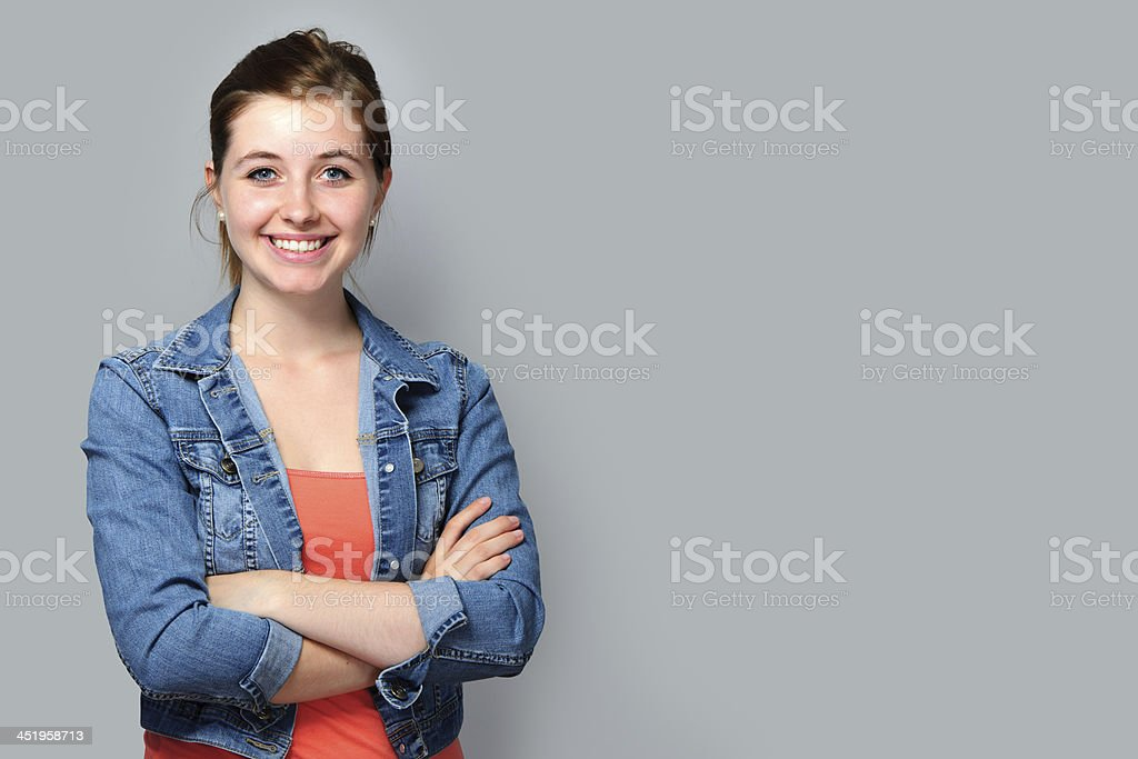 Young woman smiling wearing denim jacket with arms folded stock photo
