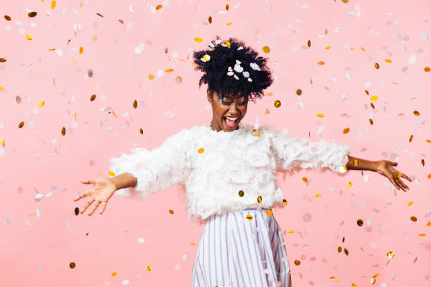young woman smiling with arms open amid confetti falling - carlos david stock pictures, royalty-free photos & images