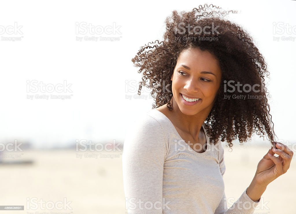 Young woman smiling with curly hair stock photo