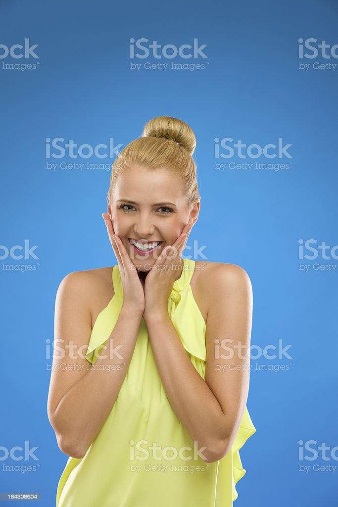 Young woman smiling with hands on chin against blue background. royalty-free stock photo