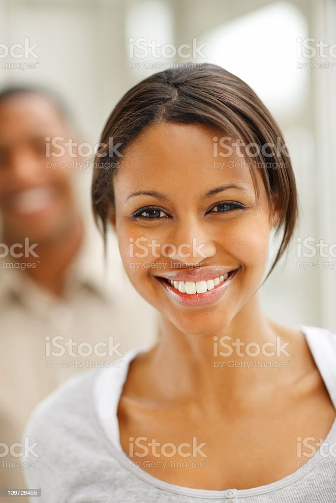 Young woman smiling with man in the background royalty-free stock photo