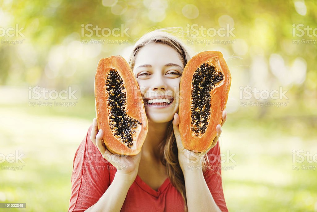 Young woman smiling with papaya stock photo