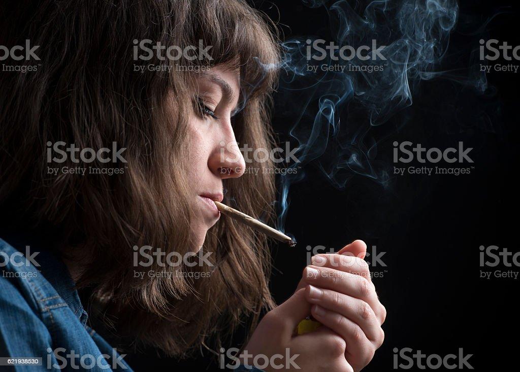 Giovane donna smokes una sigaretta - foto stock