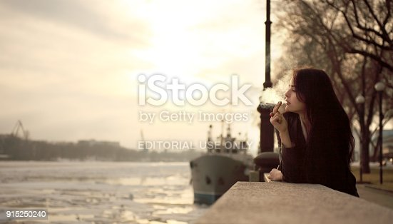 Rostov-on-Don, Russia - February 13, 2014: A young woman is standing on the bank of the river Don on a sunset background. She looks at the river and smokes a cigarette.