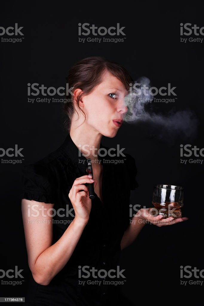 Young woman smokes e-cigarette and drinks Whiskey royalty-free stock photo