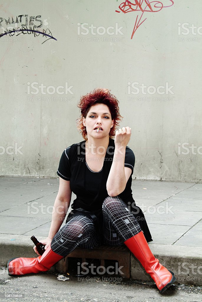 Young woman smoking and drinking in the gutter royalty-free stock photo