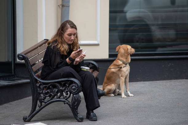 Jovem fumando e lendo uma mensagem no telefone e um cachorro amarrado a um banco na rua perto da vitrine - foto de acervo